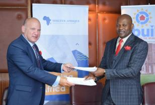 Shelter Afrique Chief Executive Officer Andrew Chimphondah right and iBUILDs Co founder and Chairman Lew Schulman exchange MOU documentsjpg