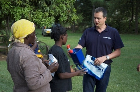 Mikkel Vestergard Frandsen shows a Family LifeStraw water filter to a recipient family. (Image source: Stephen Williams)